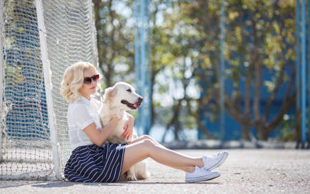 trusting: Young beautiful woman the blonde with curly hair in dark sun glasses, dressed in a white blouse and a black skirt with white stripes, spends time on the football field in the summer, playing with your favorite dog breed Golden Retriever Stock Photo
