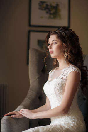 the caucasian beauty: Beautiful young woman with brown eyes, professional makeup, brunette with beautiful wedding hairstyle and tiara, ears expensive earrings, dressed in a white wedding dress sitting on the armchair in the hotel room