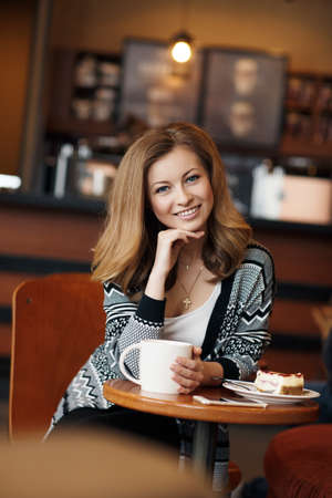 thick hair: Young beautiful woman with long, blond, thick hair and gray eyes, on the neck is a gold cross, wearing a gray jacket with a black pattern and a white t-shirt, sitting alone at a table in a cozy cafe with a big white cup of hot tea