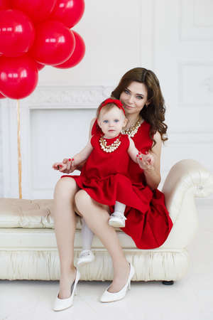 mother of pearl: Portrait of mother with little daughter on a light gray background in the Studio with balloons, mom-brunette with long curly hair and gray eyes and a little girl with short hair, a red bow on his head, both dressed in red dresses and pearl necklaces