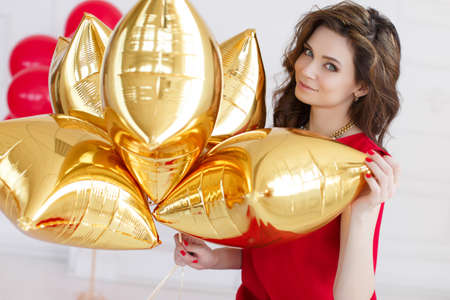 sleeveless dress: Young beautiful brunette woman with long curly hair and grey eyes, dressed in a red sleeveless dress, round neck wears a white necklace, a portrait, on light gray background in the Studio with a bunch of gold balloons - of pillows on your birthday