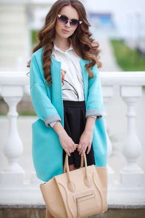 Young beautiful brunette woman with long curly hair, wears dark sun glasses, on fingers wearing a ring, dressed in a blue cloak, white shirt and black skirt, holding a leather bag beige posing outdoors in the city in the spring Stock Photo