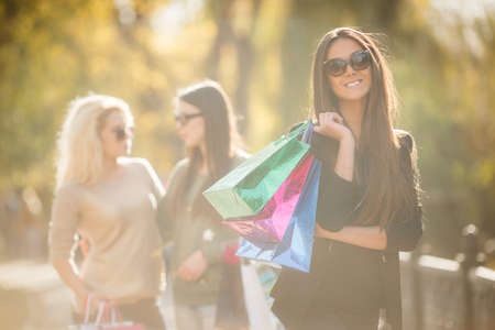 straight jacket: Beautiful slender young brunette woman with long straight hair, wearing a black light jacket, wearing dark sunglasses, posing in yellow autumn Park on a background of two friends, in the hands holding colorful paper shopping bags