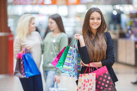 straight jacket: Beautiful slender young brunette woman with long straight hair and brown eyes, wearing a black light jacket, posing in a supermarket on the background of the two friends, in the hands holding colorful paper shopping bags Stock Photo