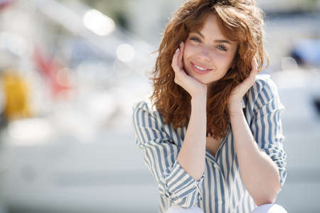 adult cruise: Stylish young woman with gray eyes, curly red hair and sweet smile, dressed in white pants and a bright striped shirt, hanging out on the dock near the yacht club sits amid sea of ??yachts and boats in summer time in fresh air Stock Photo