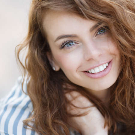 Beautiful girl with grey eyes and long curly red hair, a nice smile and straight white teeth, light makeup, wearing earrings, wearing a light striped shirt, posing for photographer during the summer in the fresh air