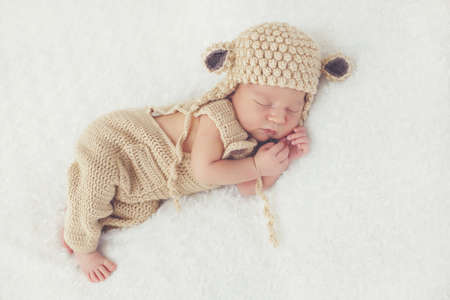 legs folded: Cute newborn baby knitted in beige overalls and a beige knitted cap with round ears, folded handle under the head and legs legs, happily sleeping on a white, fluffy, soft blanket Stock Photo