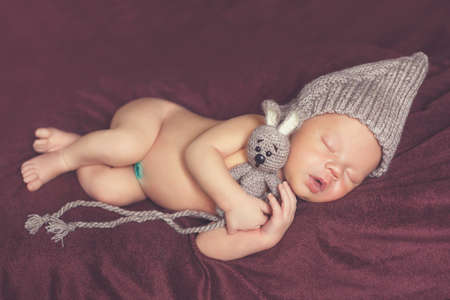 lying on his tummy: Closeup portrait of newborn baby in gray knitted hat with a grey toy Bunny, a little fluffy hair, sweetly asleep on a dark brown blanket, lying on tummy, put hands behind his head and legs under her Stock Photo