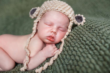 Closeup portrait of newborn baby beige knitted hat with round ears, a little fluffy hair, sleeps on the dark green blanket, lying on tummy, put hands behind his head and with legs tucked under herself