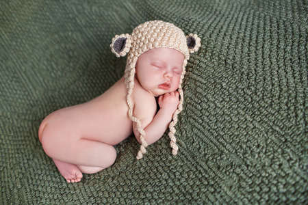 lying on his tummy: Closeup portrait of newborn baby beige knitted hat with round ears, a little fluffy hair, sleeps on the dark green blanket, lying on tummy, put hands behind his head and with legs tucked under herself
