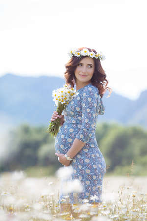 Happy pregnant brunette woman, in a blue dress with a bouquet of white daisies on his head wears a wreath of flowers white Daisy, walking in the summer field of blooming white daisies on a background of mountains and green trees