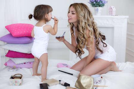 Allegro giovane madre, bionda con i capelli ricci lunghi e la sua piccola figlia, bruna, giocando insieme su un letto bianco in una camera da letto luminosa con kit per il trucco della mamma, sia vestito in mutandine bianche e magliette bianche