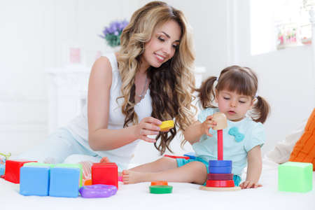 Beautiful young mother, with long blonde curly hair, playing with his little daughter in a logical educational games, pyramid and collect the colored blocks, the daughter is a brunette girl with two ponytails on her head Stock Photo