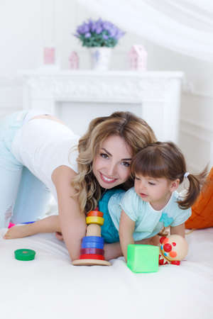 designer baby: Beautiful young mother, with long blonde curly hair, playing with his little daughter in a logical educational games, pyramid and collect the colored blocks, the daughter is a brunette girl with two ponytails on her head Stock Photo