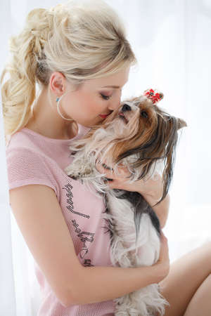 bow window: Beautiful woman, blonde hair, nice smile and light makeup, my ears gold earrings, dressed in a pink blouse, holding a beloved friend-the dog breed Yorkshire Terrier with a red bow on her head, sitting near a large bright window