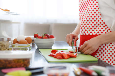 pinafore: Young beautiful woman dressed in a white shirt and white red polka dot pinafore, engaged in the bright kitchen slicing red ripe strawberries to decorate cupcakes