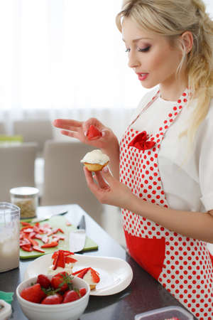 pinafore: Young beautiful woman, blonde hair, light makeup and pink lipstick, wearing earrings, wearing a white t-shirt and white red polka dot pinafore, engaged in the bright kitchen cooking cupcakes