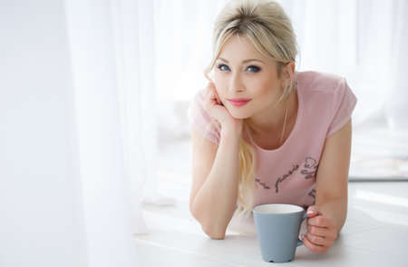 luxuriate: Beautiful young woman with long blonde hair and blue eyes, light makeup and pink lipstick, wearing a pink blouse, lying on the floor near a bright window closed white curtains with a large blue-gray Cup of hot tea Stock Photo