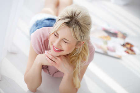 luxuriate: Beautiful young woman with long blonde hair, cute smile and straight white teeth, light makeup, wearing a pink blouse and blue shorts, lying on the floor near a bright window, white curtains closed, eyes closed and hands resting under the chin