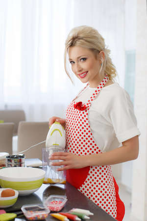 pinafore: Young beautiful woman, blonde hair, light makeup and pink lipstick, nice smile, wears earrings, wears a white t-shirt and white red polka dot pinafore, engaged in the bright kitchen cooking baking