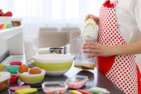 pinafore: Young beautiful woman dressed in a white shirt and white red polka dot pinafore, engaged in the bright kitchen, preparing dough for baking in a colorful silicone forms Stock Photo