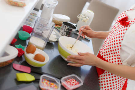 comfort food: Young beautiful woman dressed in a white shirt and white red polka dot pinafore, engaged in the bright kitchen, preparing dough for baking in a colorful silicone forms Stock Photo