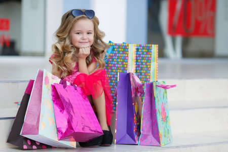 Beautiful little girl with blond long curly hair, sun glasses with glass in the form of hearts, in a pink dress with a bunch of colored shopping bags, posing sitting on the steps near the entrance to the supermarket in a big black moms shoes