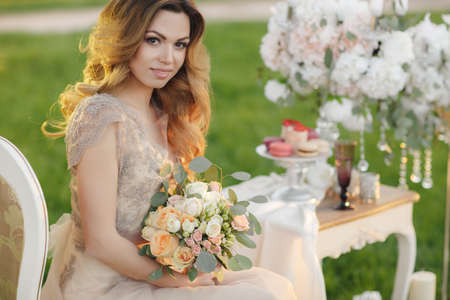 Beautiful bride, blonde woman with long curly hair and long black eyelashes, beautiful wedding dress beige in the hands holding wedding bouquet of a bride, sitting on a white chair in the summer Park near the white table with a glass of champagne Stock Photo