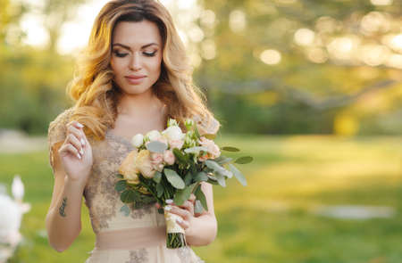 Young beautiful bride, a blonde woman with long curly hair and long black eyelashes, beautiful wedding dress beige in the hands holding wedding bouquet of the bride, posing standing in the summer Park near the white table at sunset