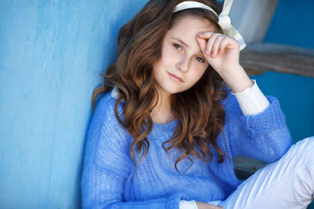 caucasian appearance: Cute teen girl, caucasian appearance, brunette with long curly hair and brown eyes, wearing a blue jacket, color white ribbon tied around, posing sitting on a ladder on a blue background outdoors in spring.