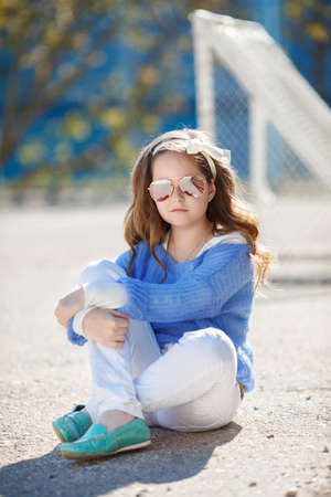 caucasian appearance: Cute teen girl, caucasian appearance, brunette with long curly hair, wearing sun glasses, wearing a blue jacket, color white ribbon tied around, spending time in the village on the football field at spring outdoor.