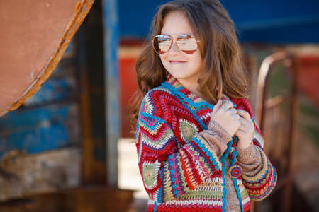 Cute teen girl, caucasian appearance, brunette with long curly hair, wearing sunglasses, wearing a long coat knitted red and blue, spending time in the countryside in the fresh air in summer, standing near a rusty truck for transportation of boats Stock Photo