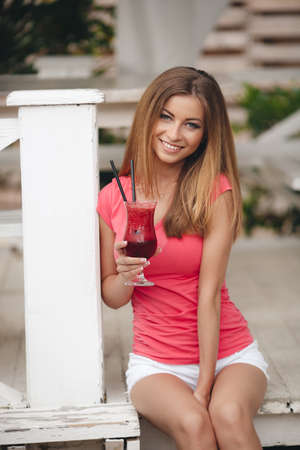 Summer portrait of a beautiful woman, brunette with long straight hair and gray eyes, a nice smile and beautiful white teeth, dressed in a red t-shirt and white shorts, resting in a country house sitting on a wooden porch with a fruity cocktail outdoors