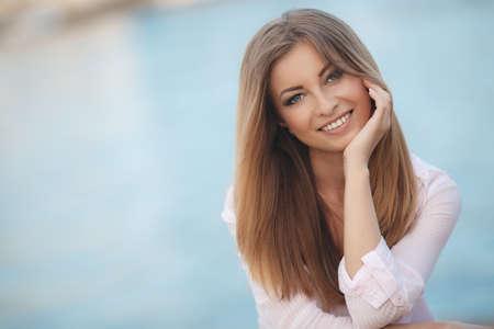 Portret van een mooie vrouw, brunette met lang steil haar en grijze ogen, een mooie glimlach en mooie witte tanden, gekleed in een wit shirt rustend op de oever van de blauwe oceaan in de zomer in de frisse lucht