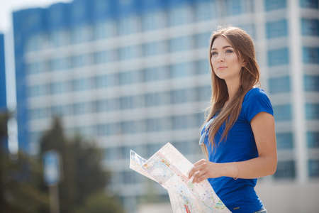 gray eyes: Pretty brunette woman with long straight hair and gray eyes, long eyelashes and light make-up, dressed in a blouse of blue color on the background of blue-white high-rise building in the hands holding a detailed map of the city