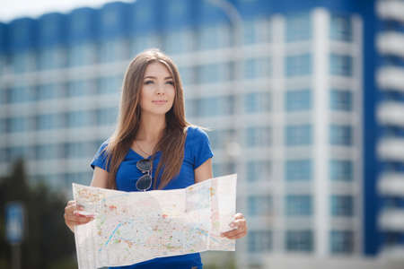 Pretty brunette woman with long straight hair and gray eyes, long eyelashes and light make-up, dressed in a blouse of blue color on the background of blue-white high-rise building in the hands holding a detailed map of the city