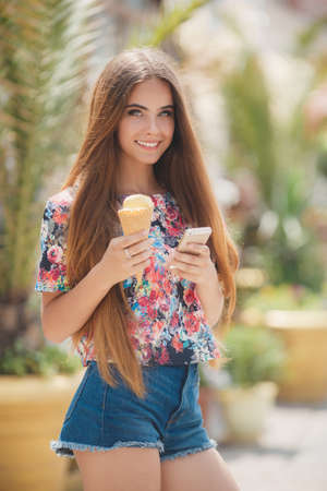 Summer portrait of a very beautiful young woman with gray eyes and long straight brown hair, a nice smile, wearing jewelry, wearing blue shorts and a colored shirt, right hand holds an ice cream cone, reads the message on the mobile phone in summer Park Stock Photo
