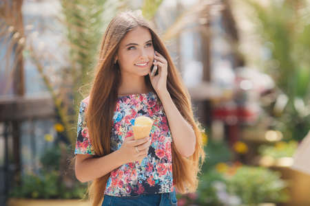 Summer portrait of a very beautiful young woman with gray eyes and long straight brown hair, a nice smile, wearing jewelry, wearing blue shorts and a colored shirt, right hand holds an ice cream cone, talking on the phone in summer Park