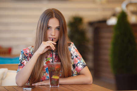 gray eyes: Portrait of beautiful young woman with gray eyes and long straight brown hair, nice smile, light makeup, wearing jewelry, wearing a colored blouse, sits alone at a table in a cafe with a glass of fruit cocktail