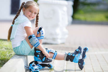 Blonde little girl with two long pigtails wearing a white t-shirt and blue shorts, wearing knee pads and protection on elbows blue, spends time alone in a city Park, roller skating black and blue in the summer