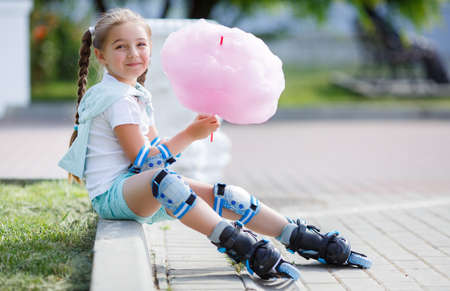 Blonde little girl with two long pigtails wearing a white t-shirt and blue shorts, wearing knee pads and protection on elbows blue, spends time alone in a city Park, roller skating black and blue in the summer, eat a sweet pink cotton candy