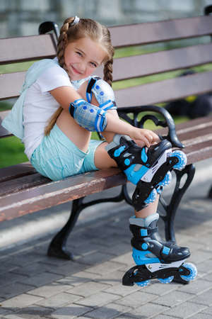 knee pads: Blonde little girl with two long pigtails wearing a white t-shirt and blue shorts, wearing knee pads and protection on elbows blue, spends time alone in a city Park, roller skating black and blue in the summer