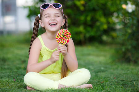 Little girl, brunette with long hair braided in two pigtails, in the ears of gold earrings, wearing sun glasses in a pink frame with glass in the shape of hearts, wearing a yellow T-shirt and pants, sitting on green grass in the summer park with a large r Stock Photo