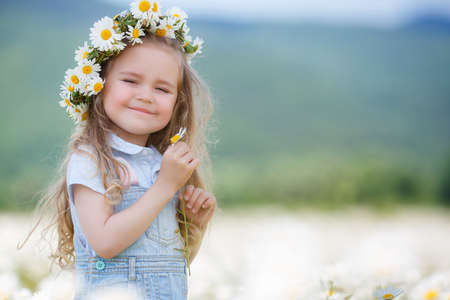 field of daisies: Beautiful little girl with long curly blond hair, cute smile, in a light blue denim overalls, a white wreath of fresh flowers, holding hands in a flower field daisies, enjoying nature in a flowering meadow white in summer