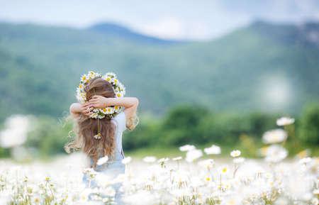 fiori di campo: Cute bambina con i capelli ricci, capelli lunghi, vestito in tuta blu chiaro e una camicia blu a pois bianchi, sulla testa indossa una corona di fiori bianchi in posa su un campo margherite bianche fiorisce in una zona montuosa in estate, vista posteriore