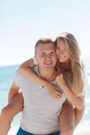 Happy loving couple, young blond man and woman having fun at the beach, the blue ocean, a girl is sitting on the back of a guy, arms around his neck, both had a nice smile, a girl wears a ring on his right hand , the guy wears a gold chain