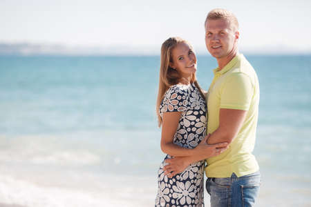 Felice giovane coppia amorosa, un uomo biondo e donna trascorrere del tempo insieme in spiaggia sulla riva del mare blu, un uomo che indossa una camicia gialla, senza maniche, una donna vestita con un abito bianco e nero, il braccio in piedi in braccio su uno sfondo di mare calmo