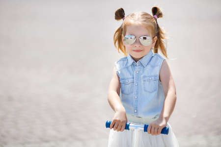 kindergartner: Little girl with blond hair, hair in two ponytails, in mirrored sun glasses, a light blue sleeveless shirt and white skirt, the one riding on the scooter in the city in the fresh air in summer