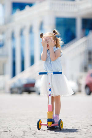 Little girl with blond hair, hair in two ponytails, in mirrored sun glasses, a light blue sleeveless shirt and white skirt, the one riding on the scooter in the city in the fresh air in summer