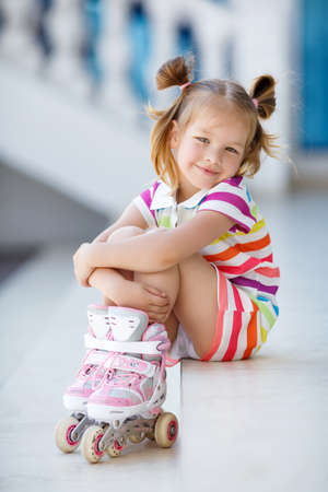 Cute little red-haired girl with hair in two ponytails, grey eyes and sweet smile, dressed in a multicolored striped dress with short sleeves, learning to roller skate in the city in the fresh air in the summer Imagens